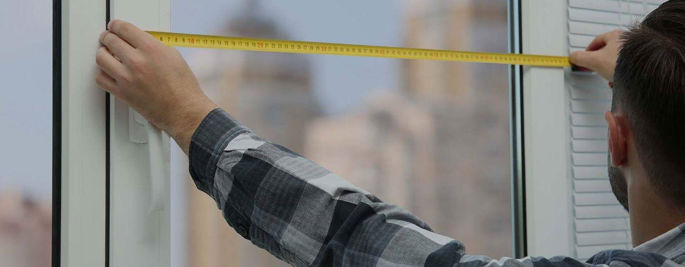 man measuring window width